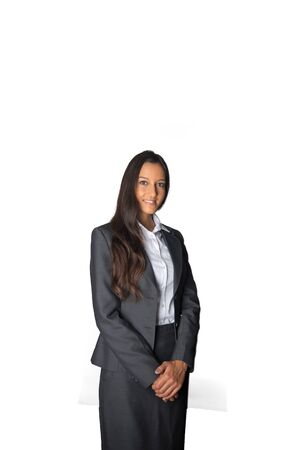 demure: Attractive Indian businesswoman in a formal pose standing with her hands clasped demurely in front of her and a friendly smile isolated on white