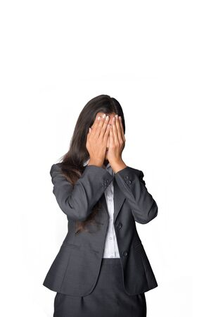 Fashionable young businesswoman covering her eyes with her hands in an effort to block out what is happening around her and not see it, isolated on white photo