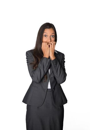 horrified: Horrified young businesswoman standing with her hands to her mouth and eyes open wide in shock, amazement or excited nail biting anticipation, isolated on white Stock Photo