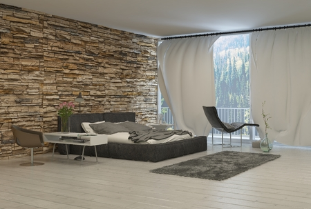 Slaapkamer met moderne meubels en bakstenen muur en bekijken van Forest vanaf het balkon Stockfoto