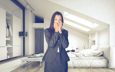 Shocked Office Woman in Business Suit inside an Architectural Room Looking at the Camera. Stock Photo