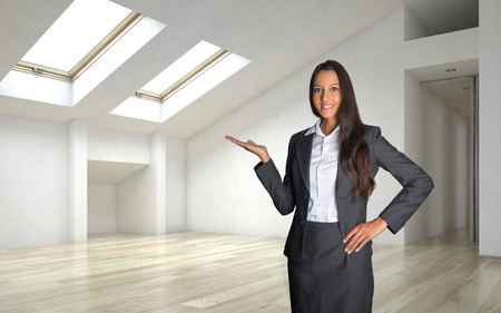 Close up Smiling Female Realty Agent in Business Suit Showing Inside of an Empty Architectural Room.
