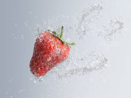 effervescence: Ripe red strawberry splashing into water with bubble effect in a diagonal direction over a graduated grey background