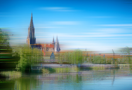 diffused: Artistic diffused image of Ulm Minster cathedral on the River Danube with the Ulm skyline against blue sky with reflections in the water