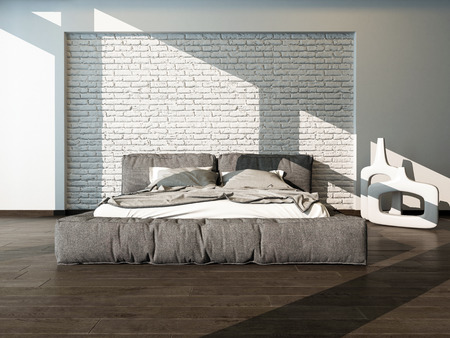 Close up of a large king size bed in a sunny bedroom with rumpled bed linen against a textured white brick wall, neutral tones