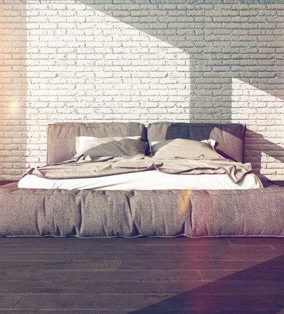 Close up of a large king size bed in a sunny bedroom with rumpled bed linen against a textured white brick wall, neutral tones with flare effect photo