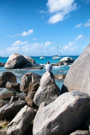 caribbean climate: Man Sitting on Boulder Alone While Viewing the Beautiful Beach in Virgin Gorda of Caribbean on a Tropical Climate.