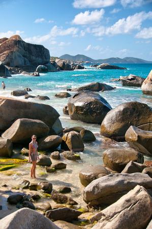 clima tropical: Sexy mujer joven posando en la playa en frente de granito de cantos rodados en la isla de Virgen Gorda en un clima tropical.