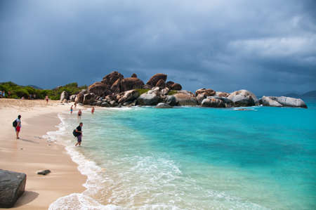 big island: Random Tourists at the the Beautiful Beach in Virgin Gorda Island with Relaxing Turquoise Sea Water Under Stormy Sky.