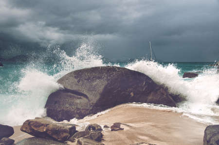 Wave breaking over a rock on a sandy tropical beach in a cloud of spray under a cloudy sky, close up view symbolic of summer vacations photo