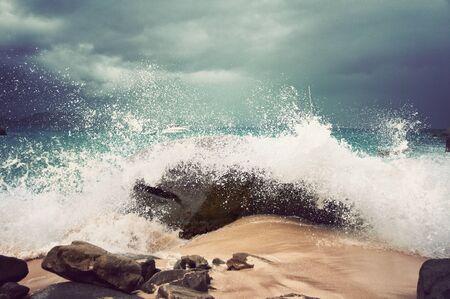 granola: Ola rompiendo sobre una roca en una playa tropical de arena en una nube de pulverización bajo un cielo nublado, opinión del primer símbolo de las vacaciones de verano