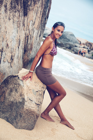 bikini slender: Happy attractive slender young Indian woman in a bikini and skirt relaxing against a rock on a tropical beach enjoying a summer vacation Stock Photo