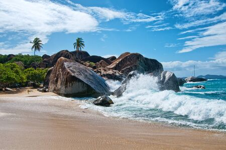 Water Splash at the Attractive Beach of Virgin Gorda Island with Big Rocks, Plants and Trees on a Tropical Climate. Stock Photo