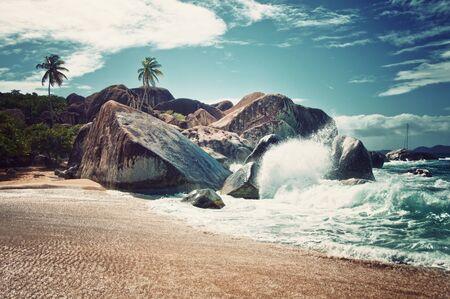 clima tropical: Splash de agua en la atractiva playa de Virgen Gorda Island con grandes rocas, plantas y �rboles en un clima tropical.
