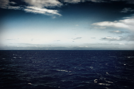 atmospheric: Dark moody ocean background with a calm sea and atmospheric deep blue gradient to the sky