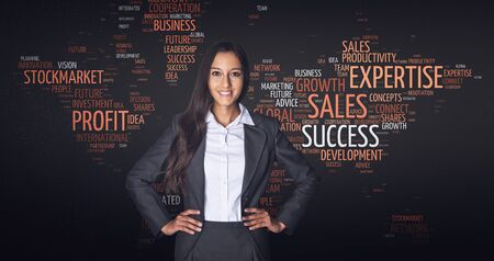 keyword: Confident Happy Businesswoman with Both hands on the Waist Standing in Front of a World Map in a Word Cloud Design with Business Tags. Stock Photo