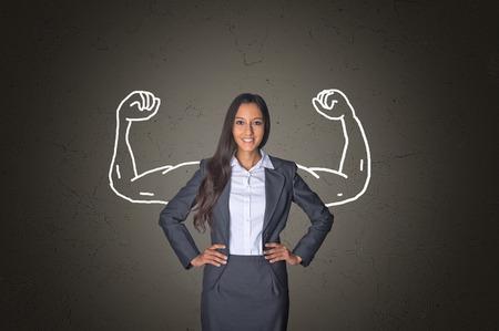 liderazgo empresarial: Conceptual Sonreír joven empresaria de pie delante de fondo gris degradado con los músculos del brazo Dibujo, Destacando Poder. Foto de archivo