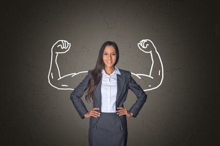 Conceptual Smiling Young Businesswoman Standing in Front Gray Gradient Background with Arm Muscles Drawing, Emphasizing Power. Archivio Fotografico