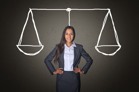 Conceptual Confident Young Businesswoman on a Gray Gradient Background with Balance Justice Scale Drawing. Stock Photo