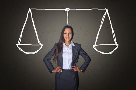 Konzeptionelle Überzeugte junge Geschäftsfrau auf einem grauen Farbverlauf Hintergrund mit Gerechtigkeit Gleichgewicht Zeichnung skalieren.