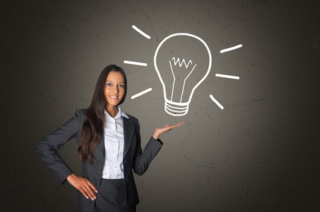 Smiling Young Executive Woman Showing Conceptual White Light Bulb Drawing on an Abstract Gray Gradient Background photo