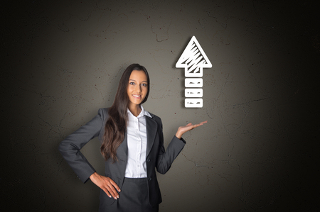 headway: Confident Young Office Woman Showing White Arrow Up Drawing on Abstract Gray Gradient Background. Stock Photo
