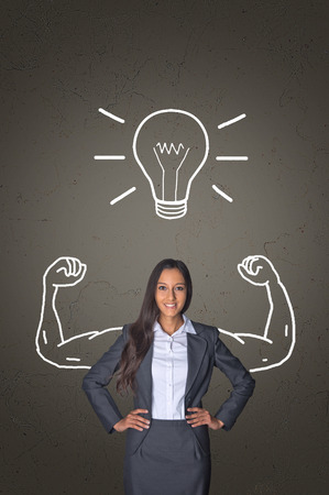 Confident Young Office Woman Smiling In Front of Gray Gradient Background with Conceptual Arm Muscles and Glowing Bulb Drawing. Stock Photo
