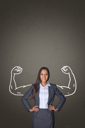 assertive: Successful businesswoman flexing her muscles in a conceptual image of power, management and leadership with hand-drawn flexed muscular arms of a body builder behind a an attractive professional woman Stock Photo