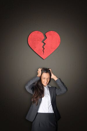 lovelorn: Young Businesswoman in Despair Tearing her Hair with Conceptual Red Broken Heart Above her on Abstract Gray Gradient Background. Stock Photo