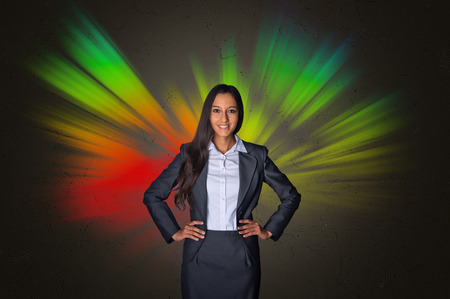 Young Happy Businesswoman in Front Attractive Abstract Radiating Colors on Abstract Gray Gradient Background. Stock Photo