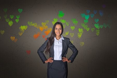 assertive: Smiling Young Businesswoman on Gray Gradient with Conceptual Colored Hearts Pattern Design. Stock Photo