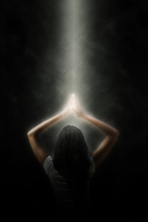 Spiritual portrait of a meditating woman in a beam of light shining down through the darkness to illuminate her hands in prayer above her head in a glow of enlightenment as she practices her yoga