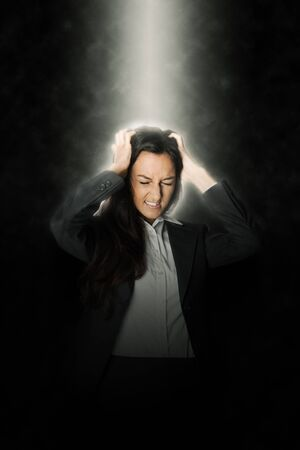 anguish: Frustrated young businesswoman tearing her hair in anguish as she stands illuminated from above by a beam of light in the darkness, conceptual image Stock Photo