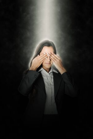attempts: Young businesswoman standing covering her eyes in a ray of light from above as she attempts to block out her surroundings to visualise a project Stock Photo