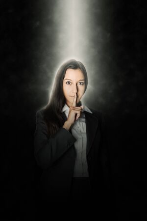 shushing: Pretty young businesswoman making a shushing gesture holding her finger to her lips as she asks you to keep a secret and remain quiet while standing in a single beam of light in the darkness