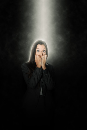 intimidated: Terrified woman standing in a beam of white light shining down through the darkness from above looking at the camera with terror in her eyes and biting her nails in suspense