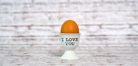 devotions: One Brown Egg in a White Porcelain Cup with I love You Texts on a Wooden Table with Abstract Background.