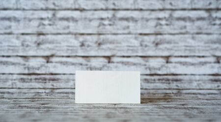 notelet: One Blank Rectangular Greeting Card Standing on a Wooden Table with a Vintage Wall Background.