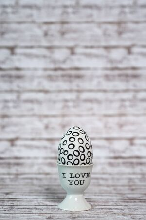 emphasizing: Close up One White Egg with Black Hollow Circles in a Cup with I love You Texts, Placed on Wooden Table, Emphasizing Copy Space.