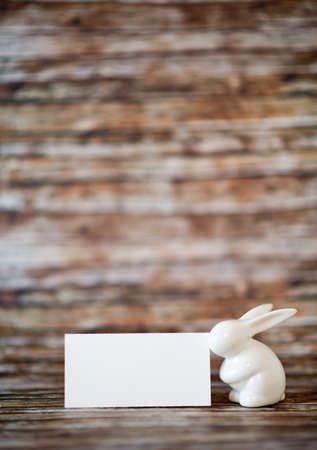 emphasizing: Close up Easter Bunny Figurine with Blank White Greeting Card on Top of a Wooden Table with Blurry Background, Emphasizing Copy Space.