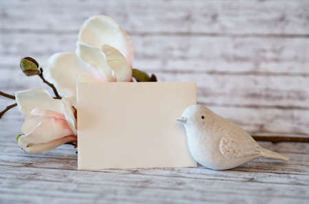 white bird: Small White Bird Figurine with Blank Horizontal Card and Blossoms on Rustic Wooden Background