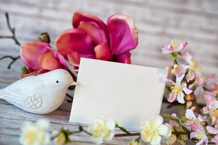 fragile peace: White Bird Figurine beside Blank Horizontal Card with Copy Space and Colorful Spring Blossoms Stock Photo