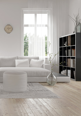 Corner of a comfortable white modern living room with an upholstered sofa and ottoman on a wood floor and bookcase full of books alongside a tall window