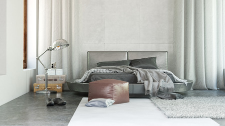 Luxury bedroom interior with grey decor and a contemporary upholstered bed flanked by long drapes with scattered throw rugs , an ottoman and lamp photo