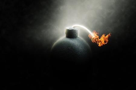 bombe: Lit bombe rond noir avec une m�che enflamm�e compte � rebours � la d�tonation illumin�e dans un puits de lumi�re qui brille dans les t�n�bres, image conceptuelle