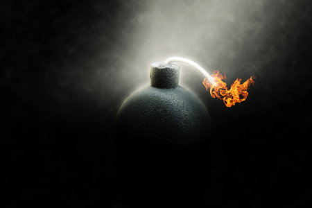 Lit round black bomb with a burning fuse counting down to detonation illuminated in a shaft light shining through the darkness, conceptual image photo