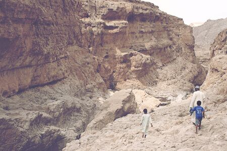 Father walking with his sons in the gorge of the Wadi Bani Khalid near Muscat Oman traveling on foot through the rocky barren terrain above the perpetual stream photo