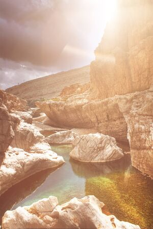 Sun flare over a rock pool in Wadi Bani Khalid lighting up the colorful rocks below the surface of the water, Muscat Oman photo