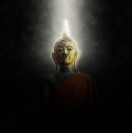 cabeza de buda: Jefe de una estatua de Buda iluminado por un rayo de luz que brilla a través de la oscuridad en un concepto espiritual de la iluminación