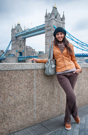 casual attire: Pretty Smiling Young Woman in Casual Attire Posing with Famous Tower Bridge Background in London.